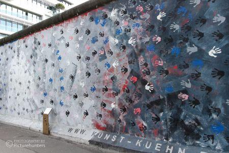 Hände auf der Mauer